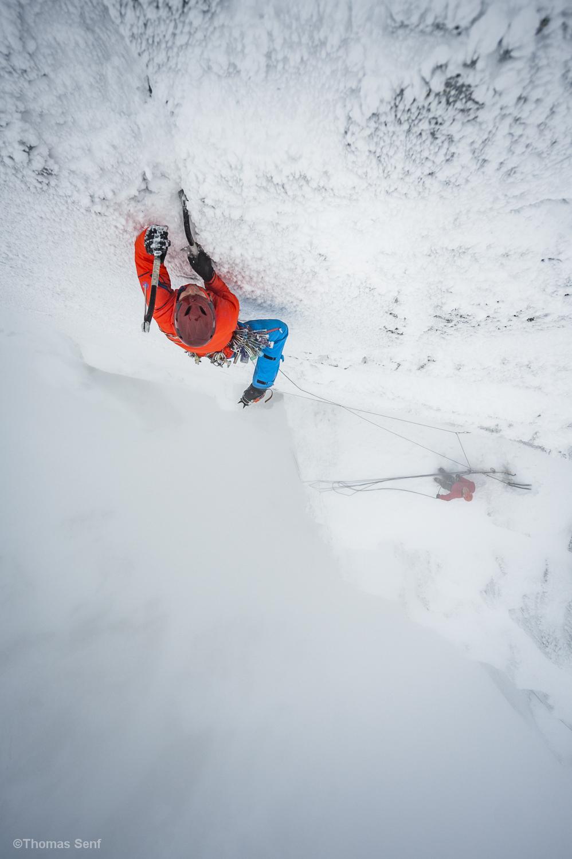 Mann klettert mit Eisäxten im Schneesturm eine vereiste Wand.