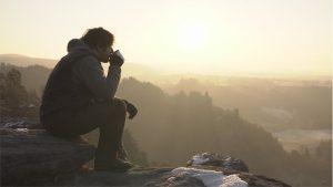 Mann mit Kaffeetasse auf verschneiter Aussicht im Elbsandsteingebirge