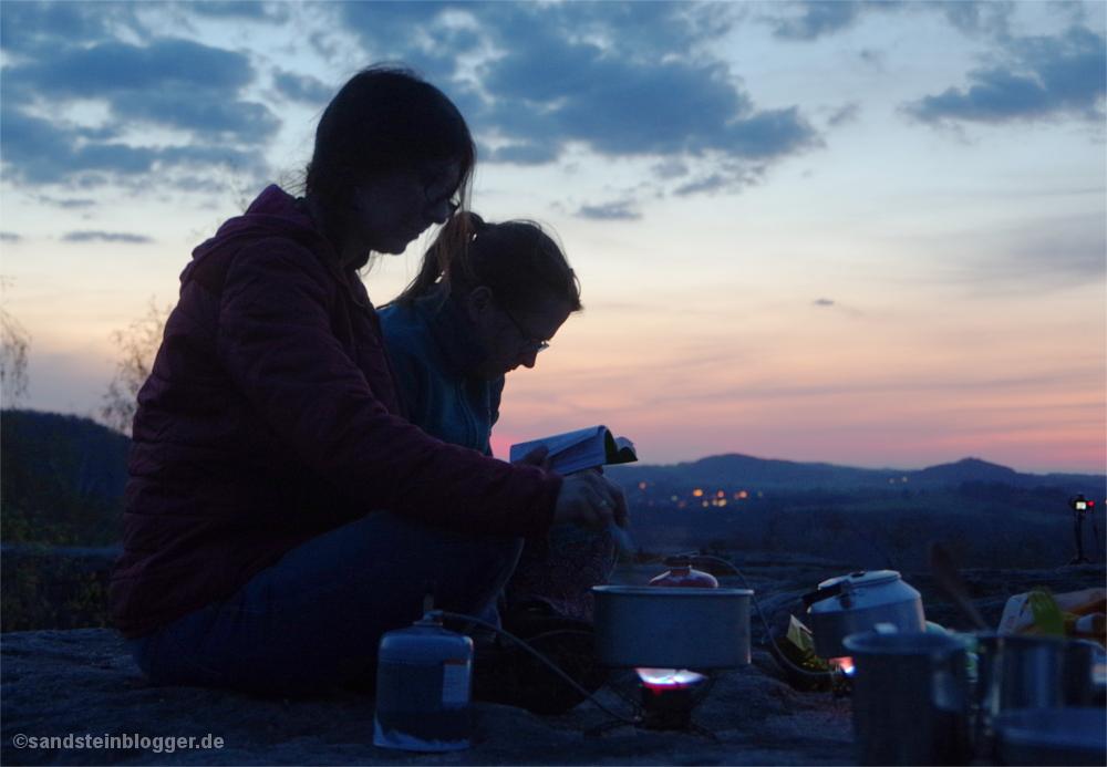 Zwei Frauen sitzen auf einem Felsplateau mit Kochgeschirr und Gaskocher