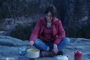 Frau auf Felsplateau vor Kochtopf