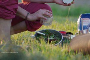 Frau gießt Dressing über einen Topf mit Salat