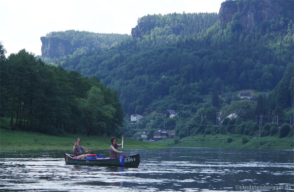 Steile Felswände hoch über dem Fluss, davor Frauen im Kanu