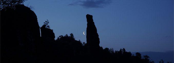 Mond, silhouettenhafter Felsen