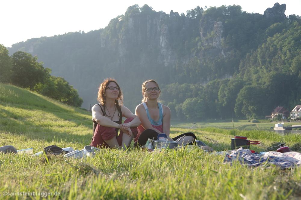 Zwei Frauen sitzen im Gras, im Hintergrund die Felsmassive bei Rathen