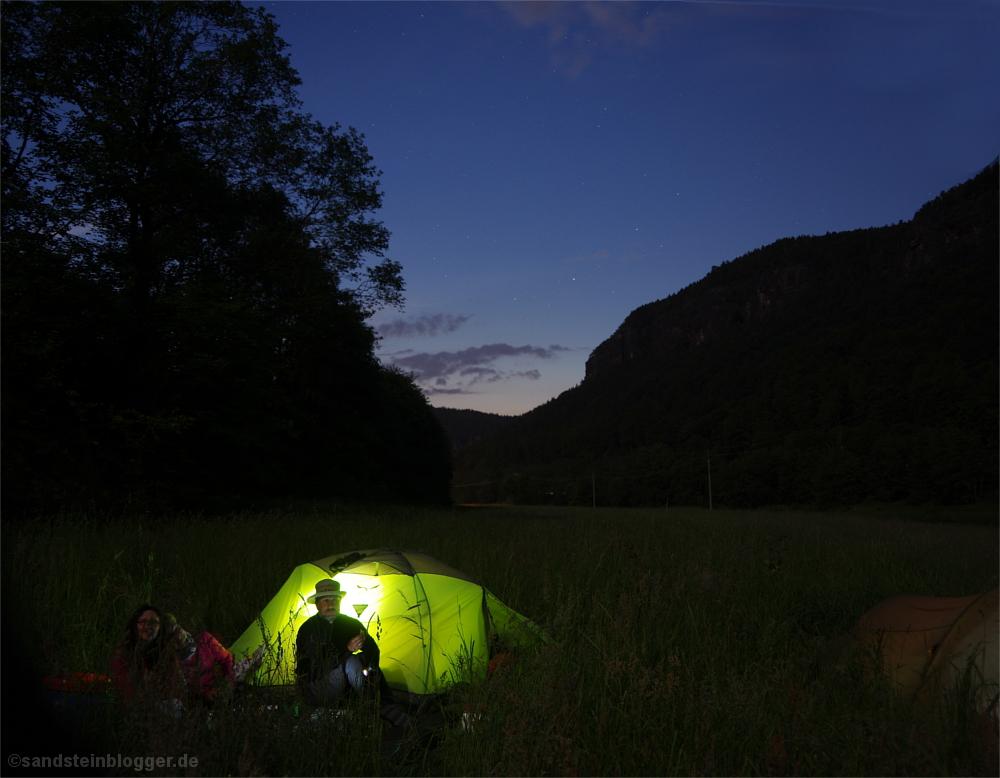 Von innen beleuchtetes Zelt, davor zwei Frauen und ein Mann, Nachthimmel, schemenhafte Felsen