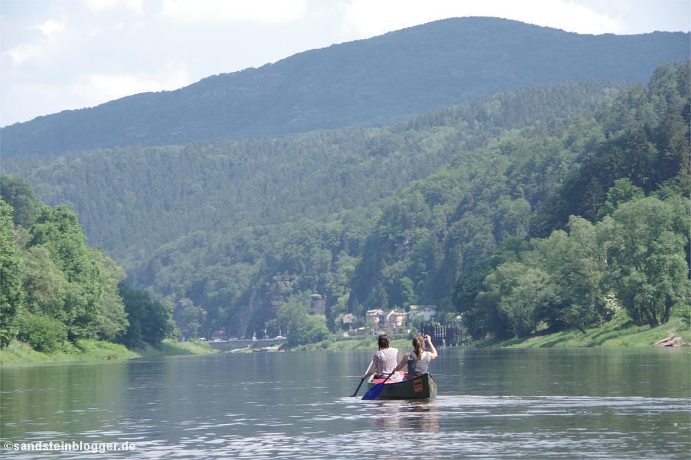 Zwei Frauen paddeln im Kanu den Fluss hinunter, am Ufer eine runde Bergkuppe