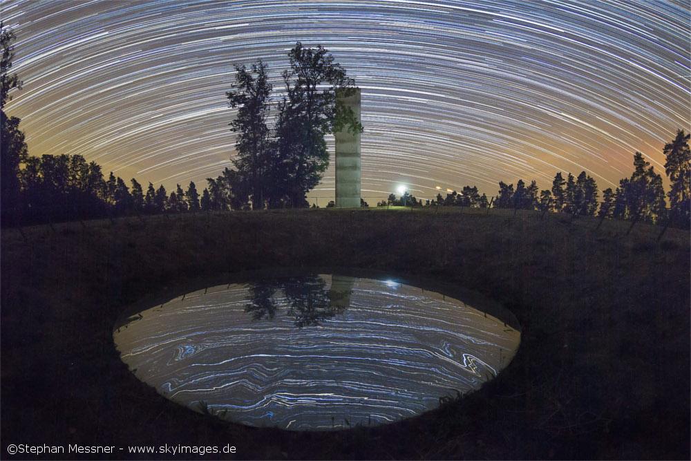 Metallplatte, in der sich der Sternenhimmel spiegelt, dahinter Aussichtsturm