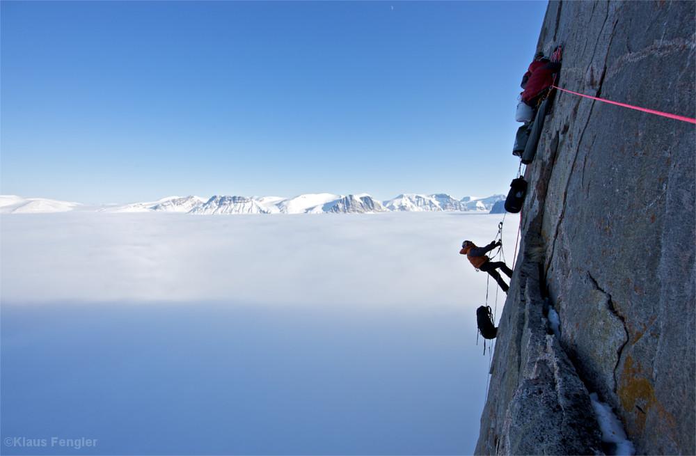 Mann in Felswand zieht einen Rucksack zu sich hinauf