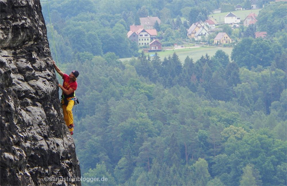 Kletterer an Sandsteinfelsen in der Sächsischen Schweiz, im Hintergrund Wälder und Häuser