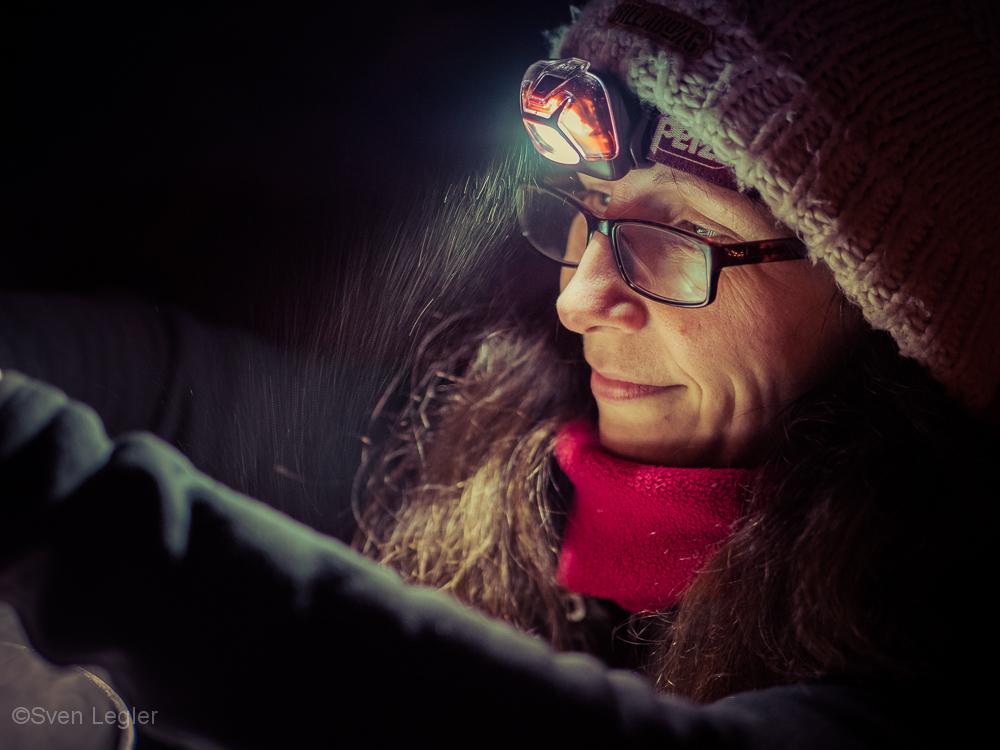 Portraitfoto - Frau mit Stirnlampe im Schneetreiben