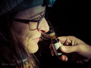 Frau riecht an einem Fläschchen mit Sandelholzaroma