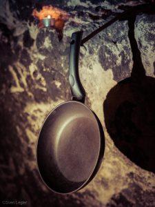 Pfanne, die an einer Felswand hängt - dahinter ein Teelicht