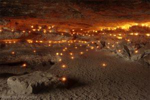 Kerzen erleuchten eine Sandsteinhöhle in der Sächsischen Schweiz