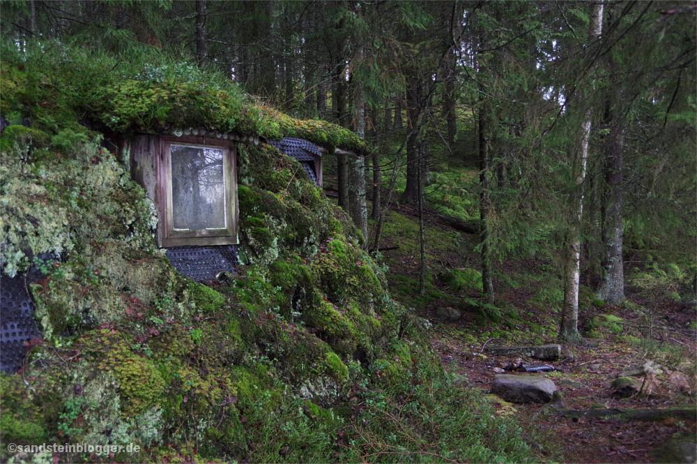 Moosbewachsene Erdhütte im Wald