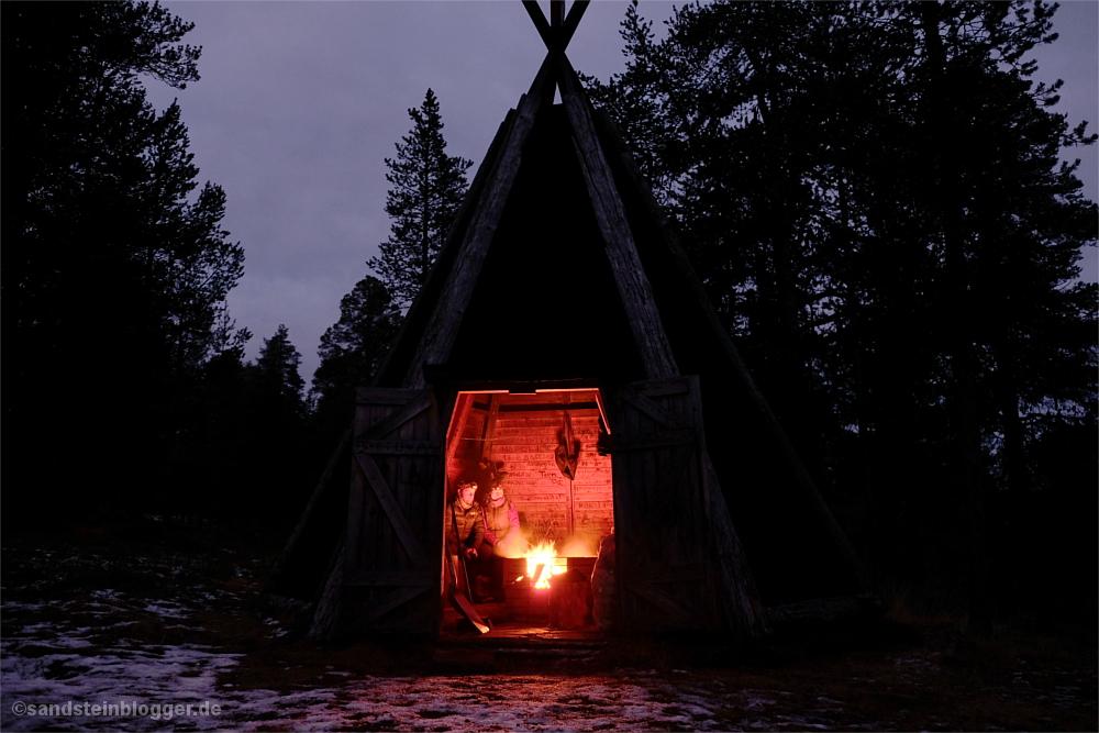 Finnische Kota, darin Mann und Frau am Lagerfeuer