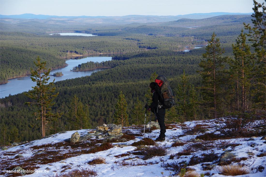Frau mit Rucksack auf einem Hochplateau über dem Flusstal des Lemmenjoki