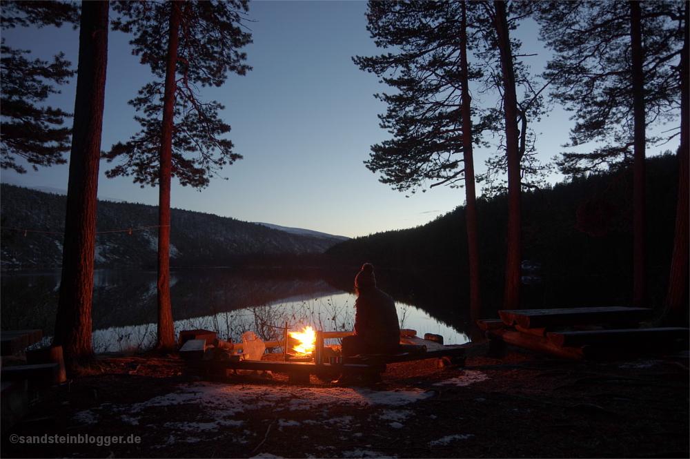 Frau am Lagerfeuer, dahinter Fluss in der Abenddämmerung