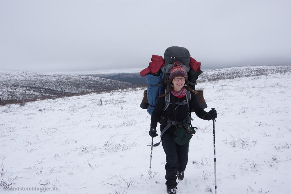 Frau mit schwerem Rucksack, endlose Schneefelder