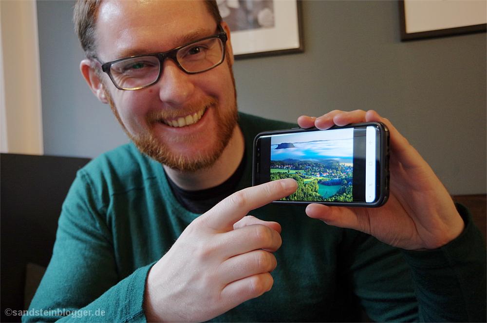 Mann zeigt auf sein Handy, auf dem ein Foto vom Lilienstein zu sehen ist.