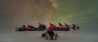 Mann liegt im Schnee. Dahinter ein Kreis von Flaggen, die den Südpol markieren. In der Ferne die Gebäude der Amundsen-Scott-Forschungsstation. Am nächtlichen Himmel tanzen Polarlichter.