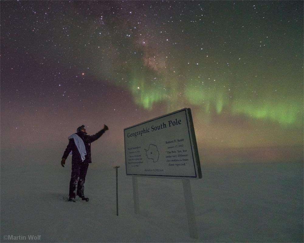 Mann steht am Südpol vor einer Gedenktafel, die an die Polarforscher Roald Amundsen und Robert Falcon Scott erinnert. Über seinem Kopf Polarlichter.