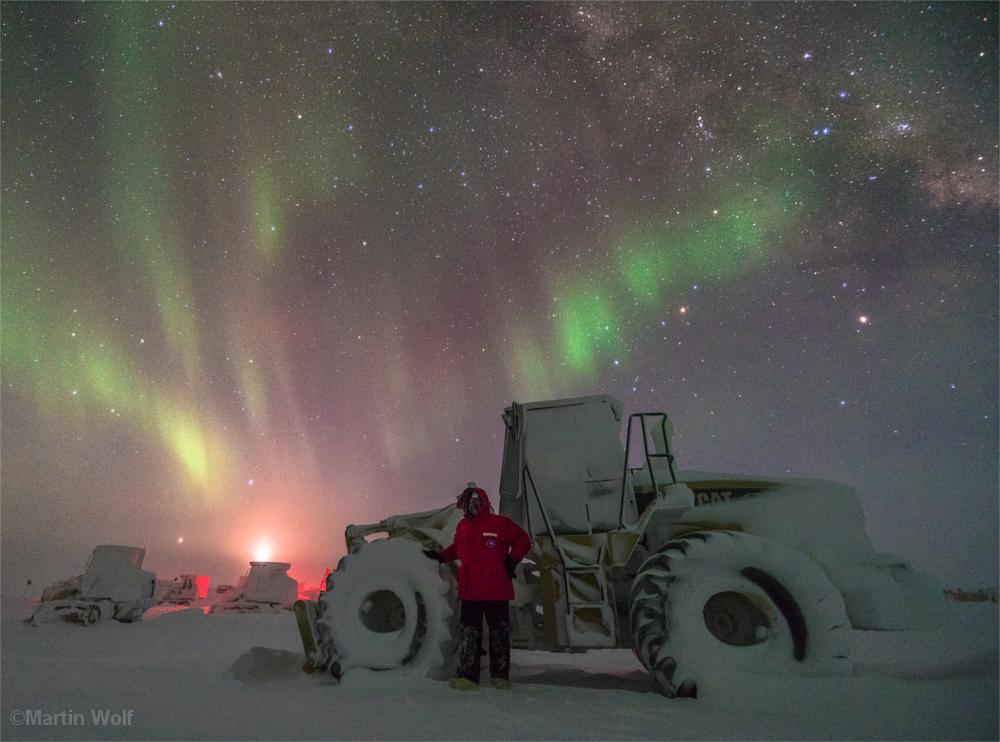 Mann vor verschneiter Schneefräse, darüber die Polarlichter