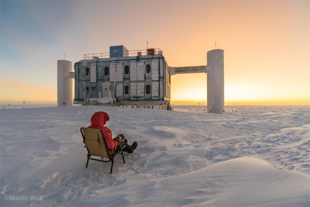 Mann in dicker Daunenjacke sitzt in einem Liegestuhl mitten auf dem Eisfeld am Südpol - vor sich einen Teil der Forschungsgebäude der Amundsen-Scott-Station.