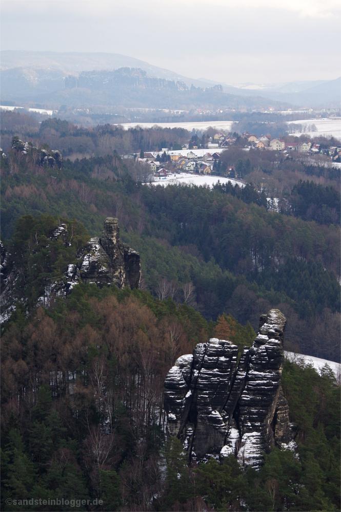 Verschneite Landschaft mit Felsen, Dörfern und Wäldern
