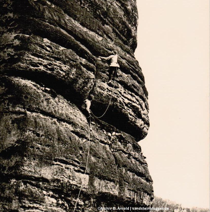 Altes Schwarzweißfoto mit Felswand und zwei Kletterern