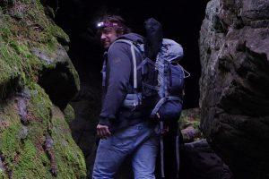 Mann am Eingang einer Felshöhle