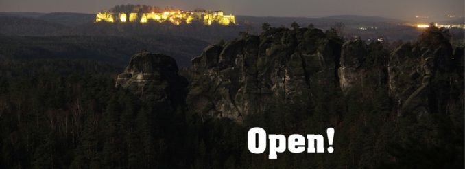 Felsmassiv bei Nacht, in der Ferne die beleuchtete Festung Königstein