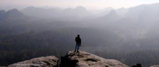 Mann auf Felsvorsprung vor Bergkulisse