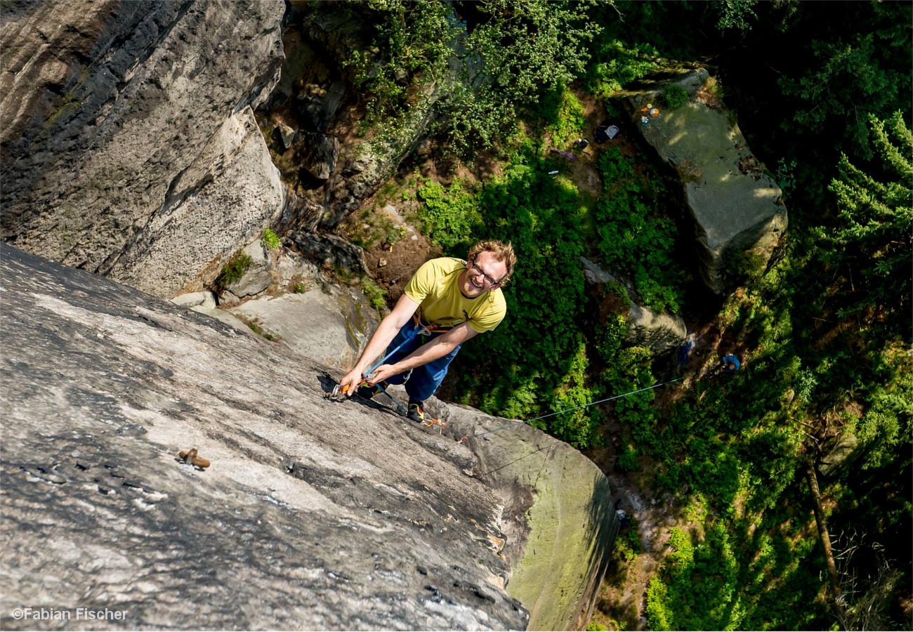 Kletterer an einem Sicherungsring in der Felswand, darunter saugende Tiefe.