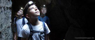 Drei Jungen mit Stirnlampe in einem Felstunnel