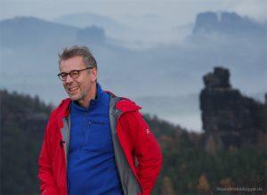 Mann vor Felslandschaft mit Nebel