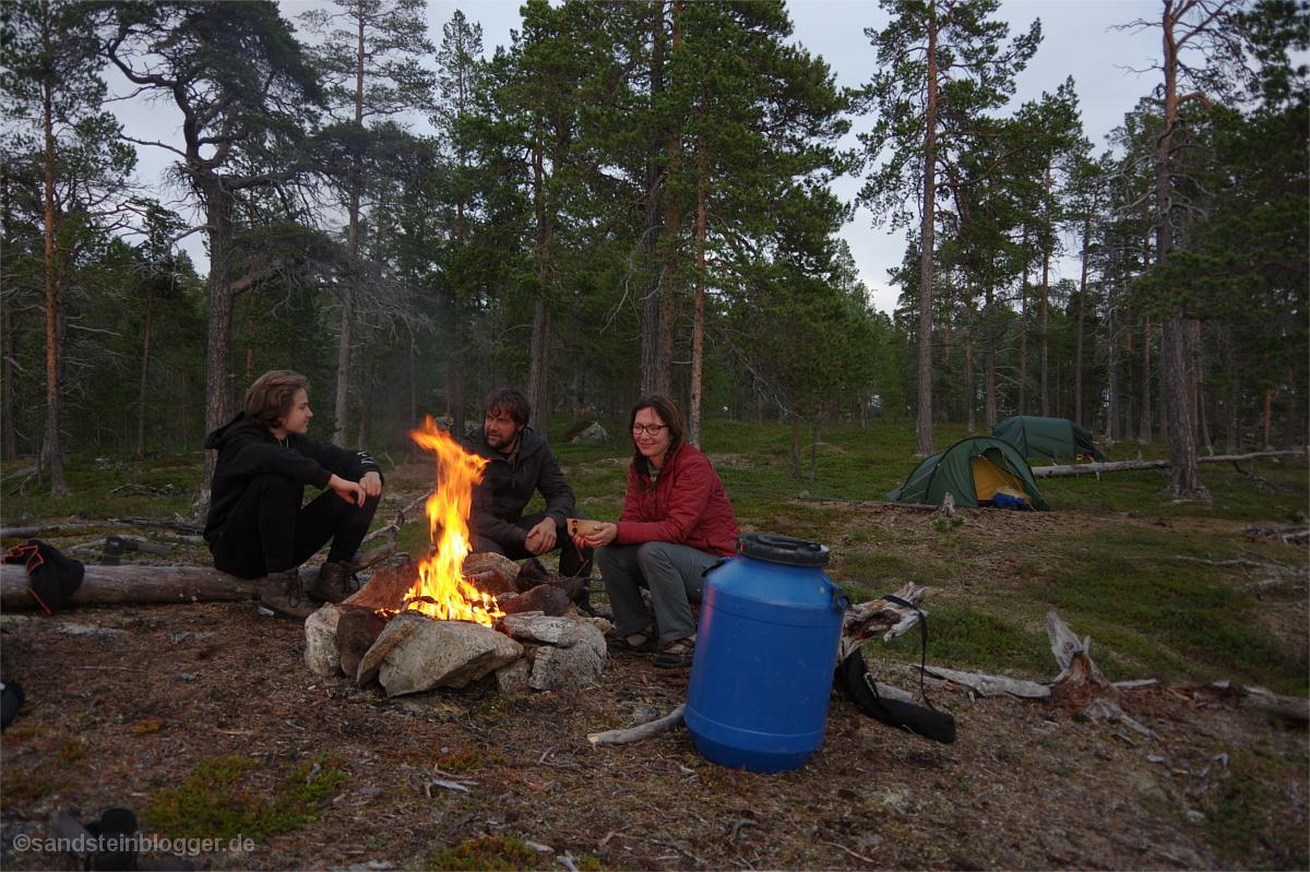 Familie am Lagerfeuer in der finnischen Wildnis