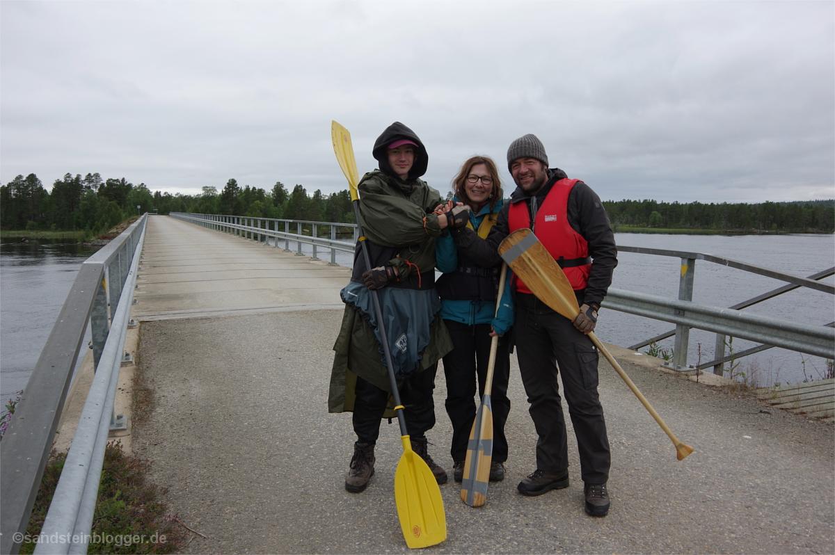 Drei Paddler auf einer Brücke an der finnisch-russischen Grenze