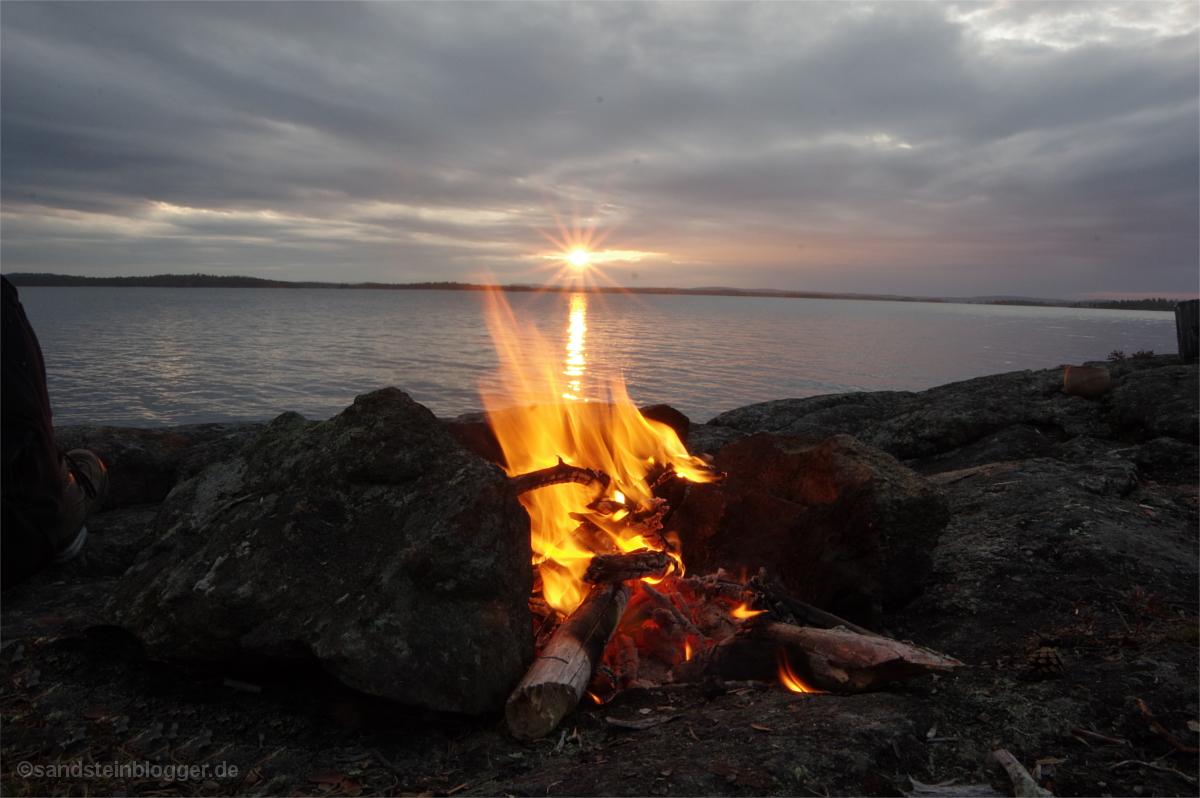 Sonnenuntergang über dem See, vorn ein Lagerfeuer