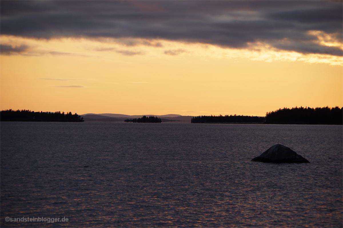 Dunkler See, orangefarbener Himmel, davor die schwarzen Silhouetten von Inseln und Landzungen