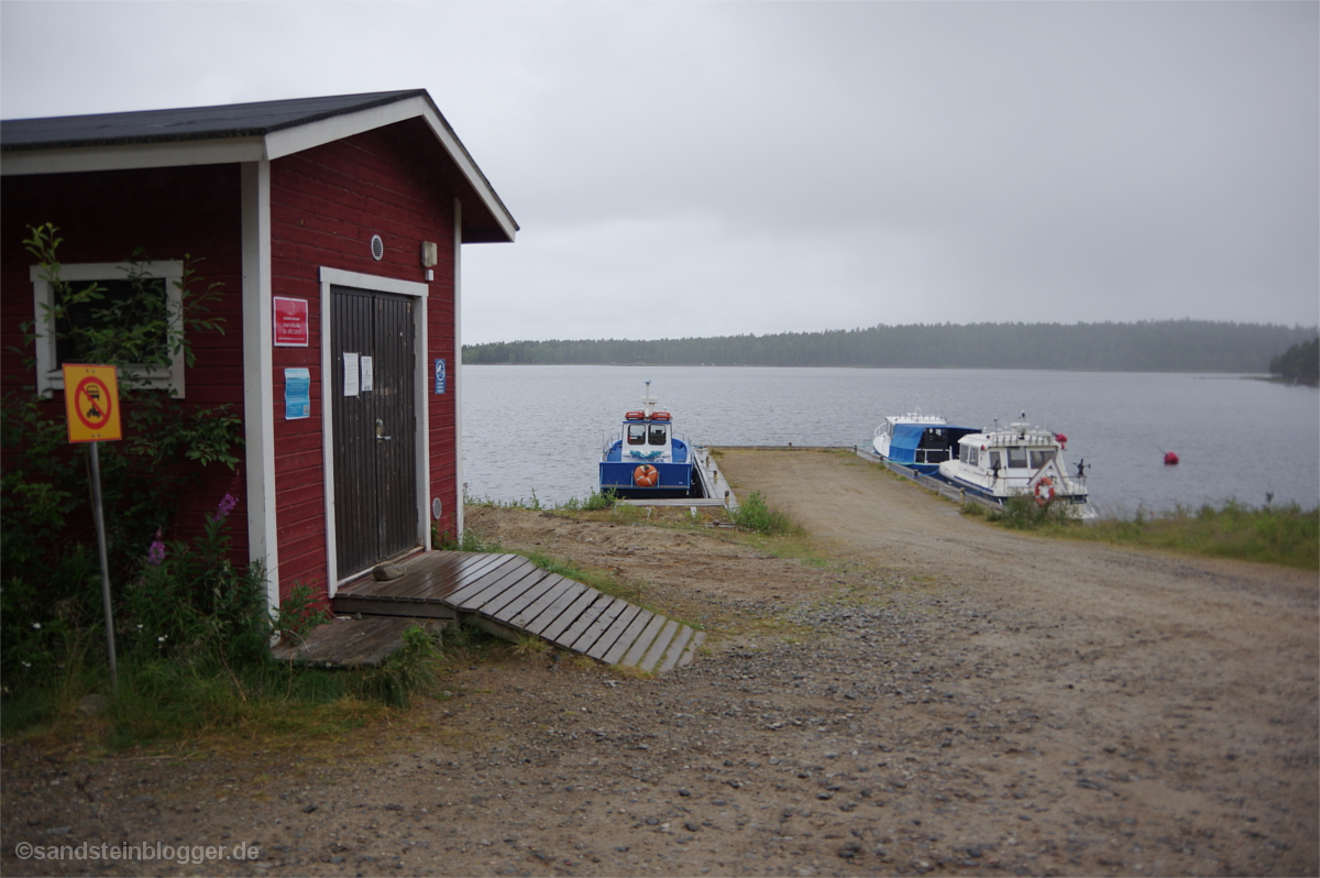 Anlegesteg mit drei Booten, vorn ein Bootsschuppen