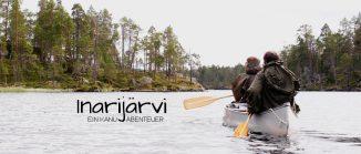 Mann und Frau im Kanu auf einem See, im Hintergrund Wildnis