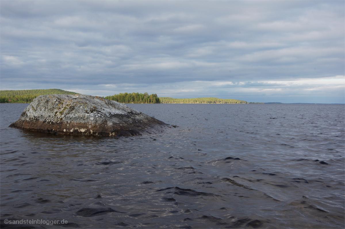 Seenlandschaft im Licht - vorne ein einzelner Felsen im Wasser