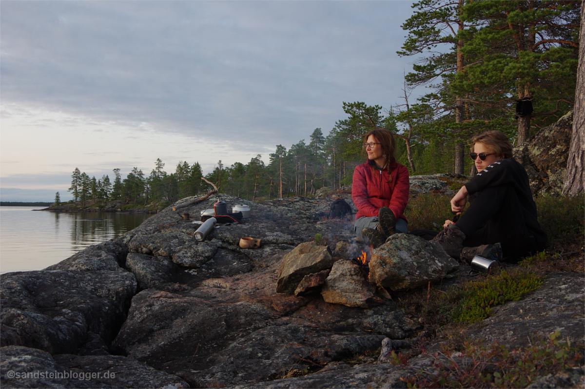 Frau und Junge am Lagerfeuer in der Wildnis