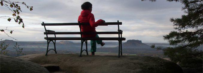 Eine Frau sitzt auf einer Bank. Von dort geht der Blick weit über die Tafelberge der Sächsischen Schweiz.