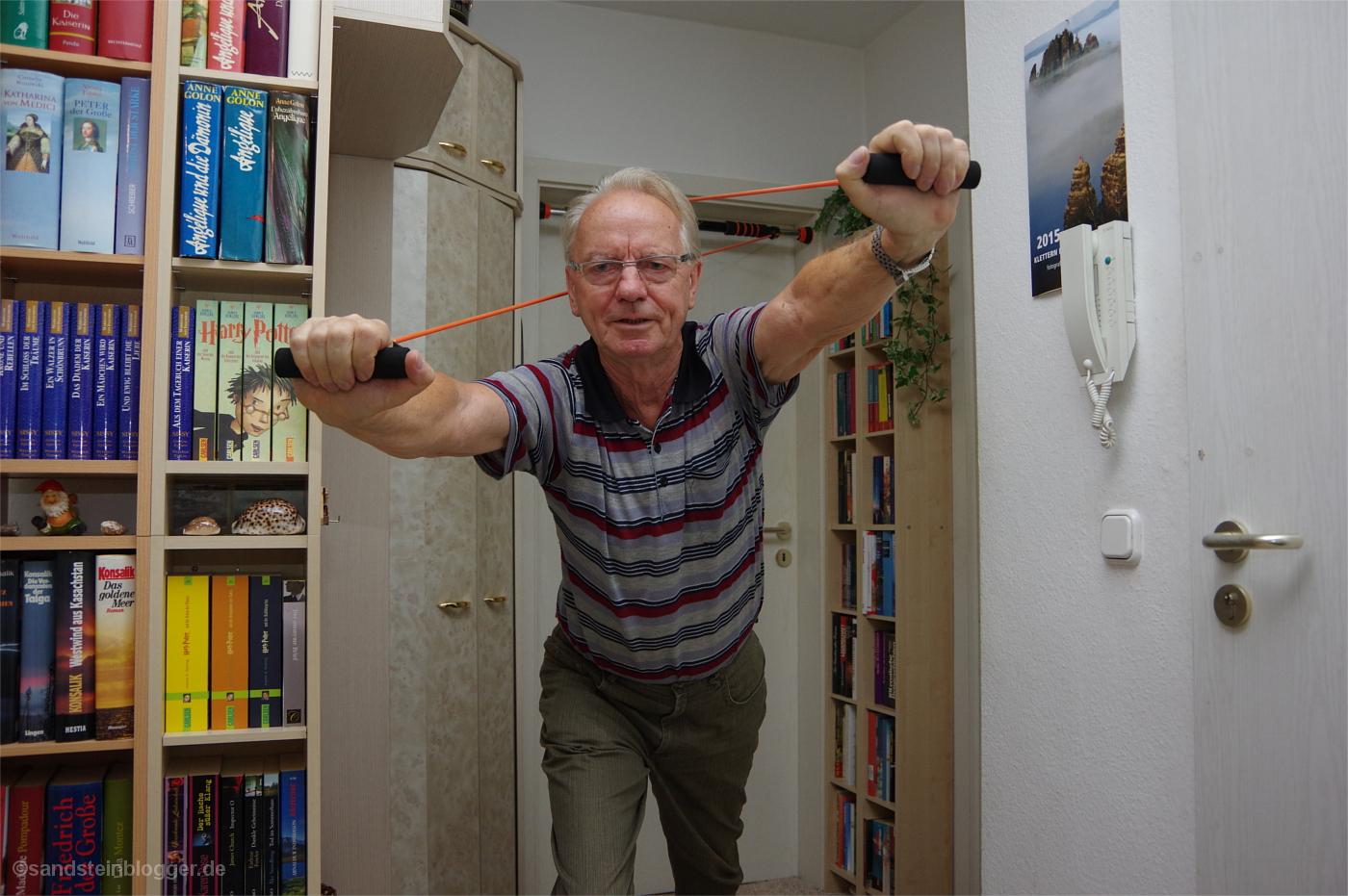 Rentner trainiert in seiner Wohnung mit Gummizugbändern