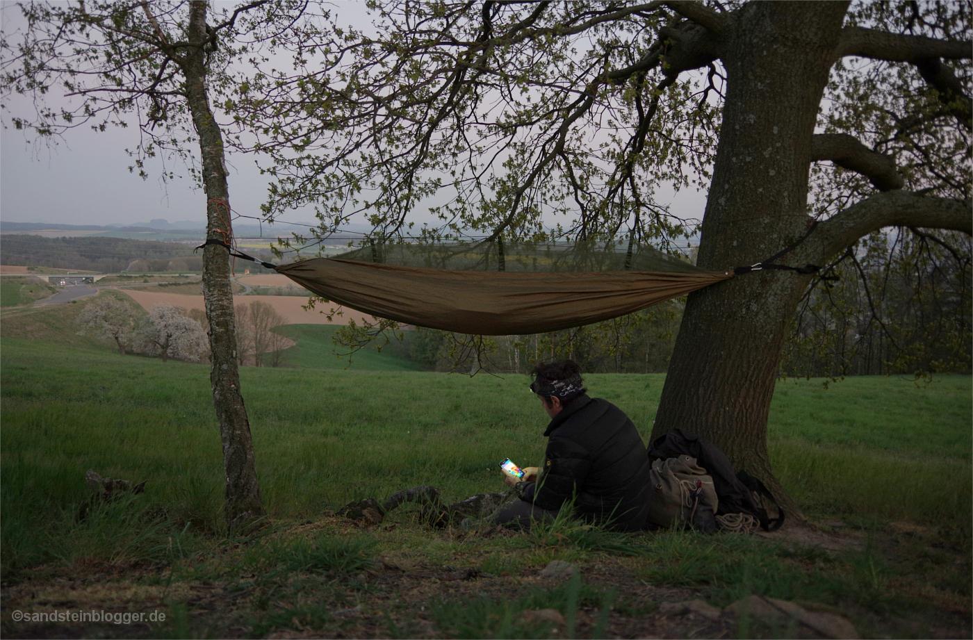Mann auf einer Anhöhe, der Blick geht weit ins Land. Zwischen zwei Bäumen ist eine Hängematte befestigt.