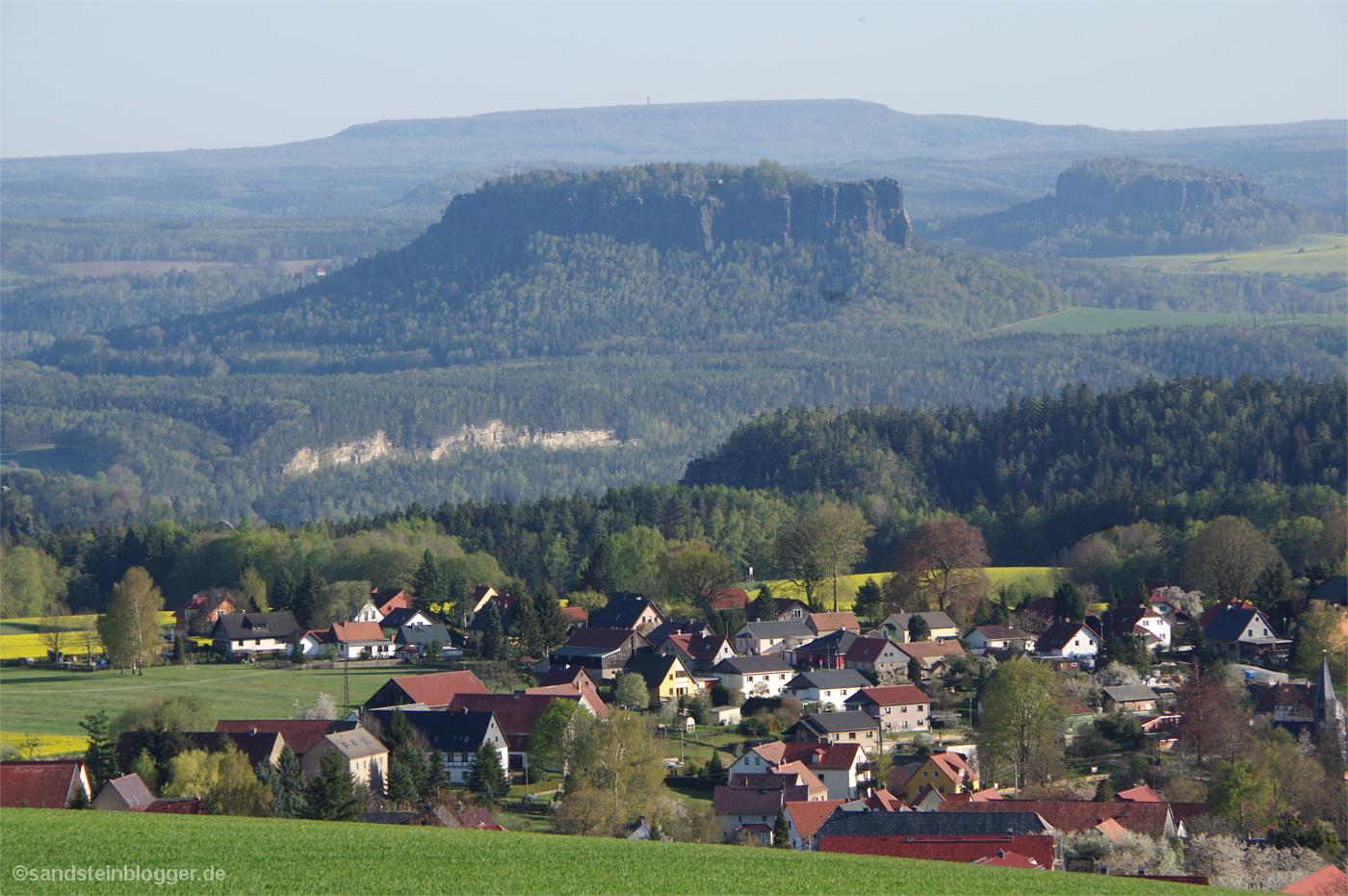 Ein Dorf, umgeben von Rapsfeldern, dahinter Tafelberge