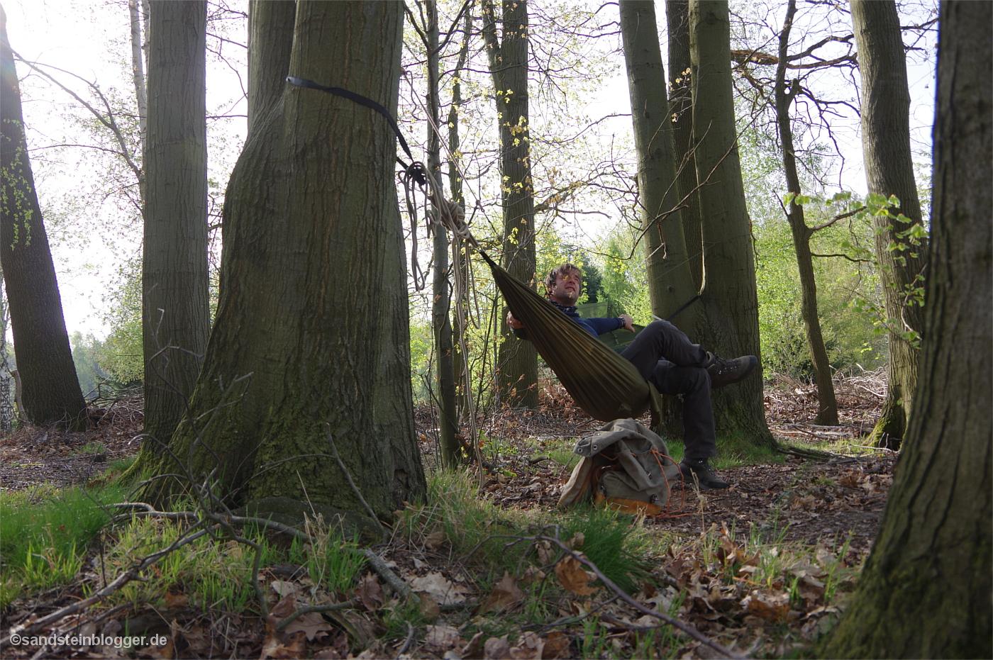 Ein Mann sitzt in einer Hängematte, ringsherum Wald