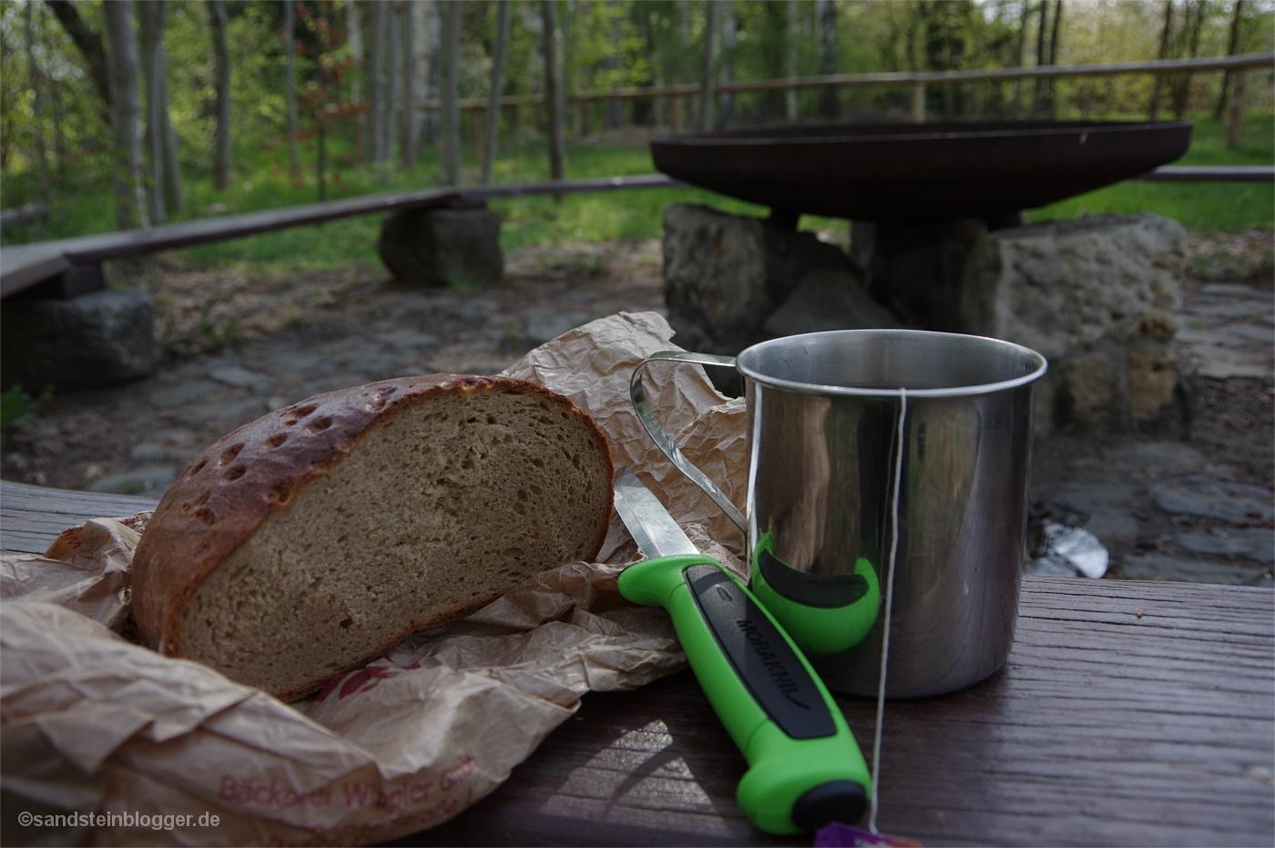 Ein Brotkanten, daneben ein Messer und eine Edelstahltasse