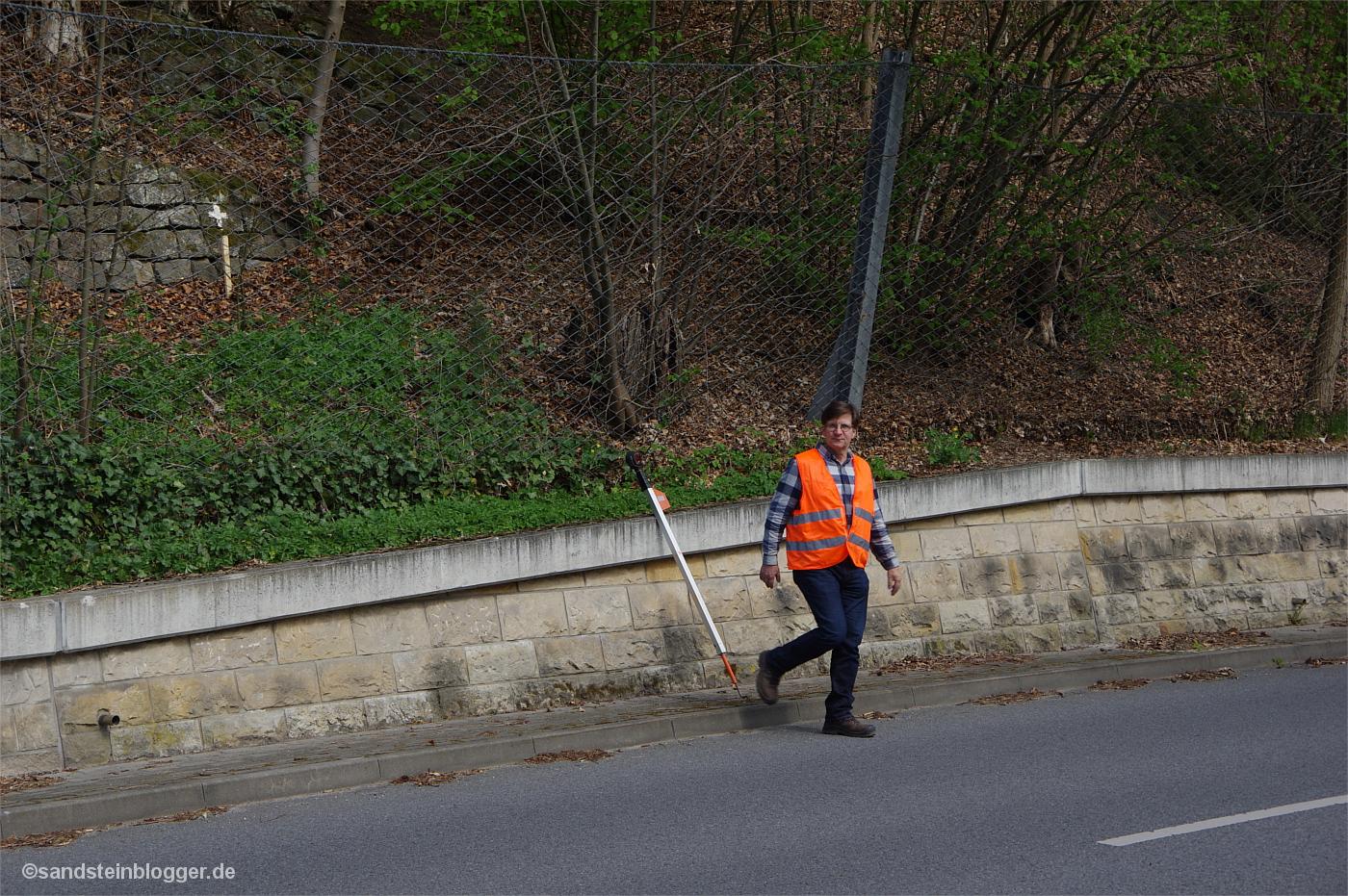 Mann mit Warnweste am Straßenrand, hinter ihm an der Böschung ei8n weißes Kreuz
